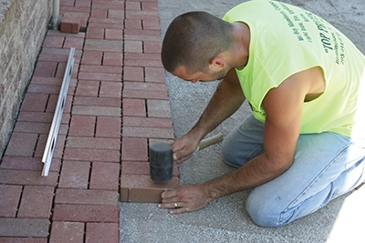 Use a rubber mallet to set the pavers firmly all joints with paver sand to lock them in place.