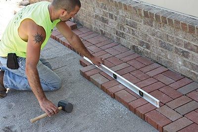 Continuously level the pavers during installation to maintain a flat walking surface and eliminate high spots.