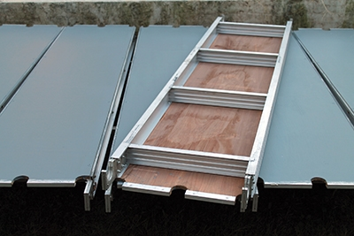 Scaffolding walk boards are built with aluminum frames and engineered not to flex, providing a stable surface for construction work.