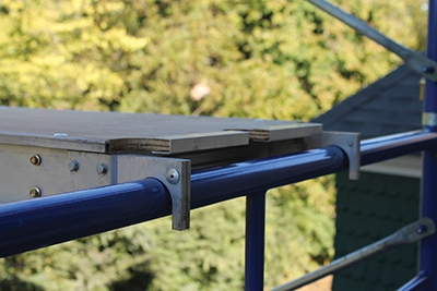 The walk boards hook over the tubular frames with a firm connection that prevents slippage underfoot.