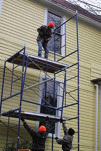 It's easiest to assemble the scaffolding with one or more person, with the lower workers passing up panels one at a time.
