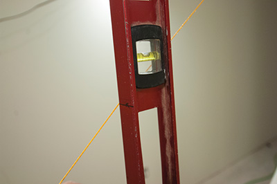 While one person holds the level plumb at the edge of the stair nose, a second person moves the string up-and-down until it intersects the mark on the level. Once at the appropriate elevation, fasten the end of the string to a nail at the floor or wall.