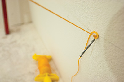 In our case, the handrail layout line terminated in the wall so we put a finish nail at a very steep angle up into the wall to make an anchor point for the end of the handrail layout string.