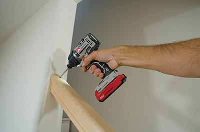 After fitting the handrail, we tacked it into the newel post at the bottom and counter-bored for a long screw where the rail meets the wall. Driving a long screw through the rail and into the framing is an important detail to make a strong connection.