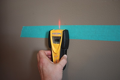 Locate and mark the studs. I make pencil marks on the painter's tape to keep the walls clean.