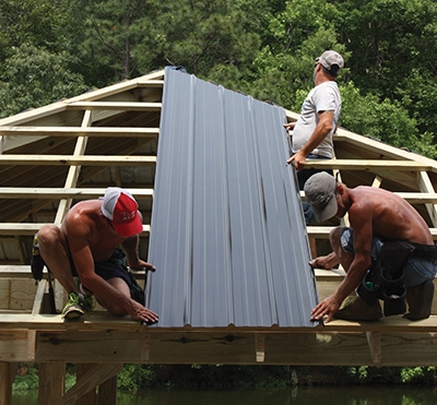 Install a corrugated panels on gable roofs usually begins on one side of the roof, working in the opposite direction of the prevailing wind. On hip roofs, this crew prefers to begin at the center and work outward. Side laps should still face away from the wind.
