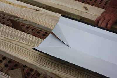 The folded ends of the ridge cap will conceal the corners of the roof for a more finished appearance.