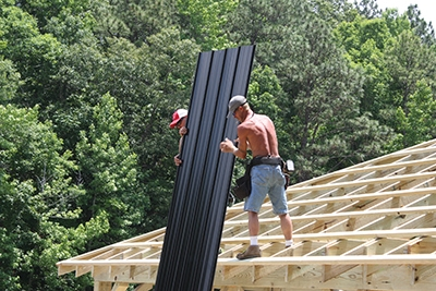 On this construction crew, one man delivers the panels to the two installers on the roof.