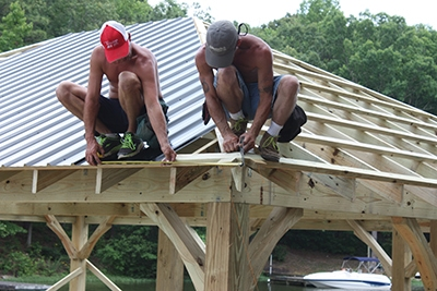 Work toward the sides of the roof deck, cutting panels to fit as necessary.