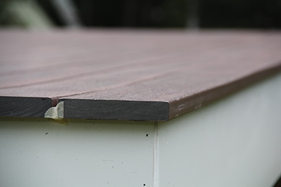 "To guide our ¾"" decking overhang, we temporarily face-nail a ¾"" board around the rim to use as a gauge. Once installation is complete, remove the board and paint/stain the rim."