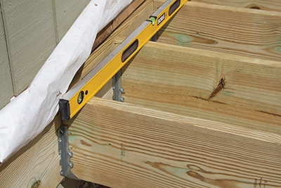 Most decks begin with a ledger board connected to the house rim joist.