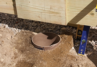 Tube-shaped cardboard forms can be cut to length and placed in the holes to pour the concrete footings.