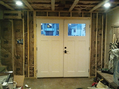 Short cripple studs fit between the header and top plate. Doubled wall studs frame each side of the door jamb. The wall is then insulated with fiberglass batts.