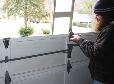 To disassemble a garage door, unscrew the individual panels one at a time, working from the top downward.