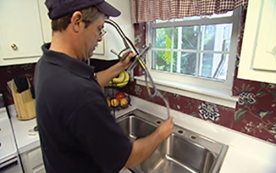 Feed the fixture through the mounting holes of the sink.