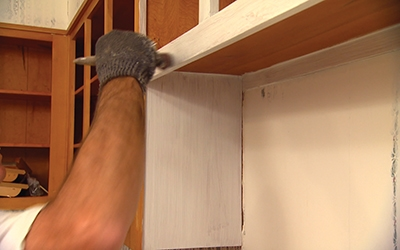 Coat the cabinets in an oil- or alkyd-based primer.