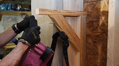 Fastening to the sides of wall studs is easy with larger shelf brackets. A few screws means you can even use the bracket to store things like my wife's tool belt.