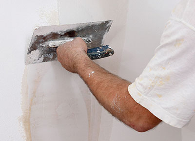 Minor wall damage can be repaired using a trowel or putty knife with lightweight joint compound or vinyl spackling. Feather the edges of the patch to blend with the wall surface.