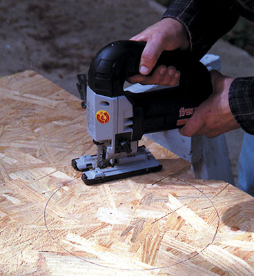 Use a compass to mark the radius for round cuts. Note the traditional D-style handle of this Freud jigsaw.