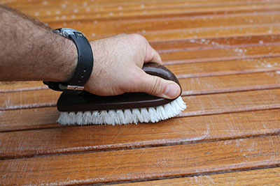 Use a soft-bristle brush to scrub in the direction of the grain.