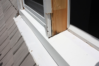 The installer shapes the aluminum on a metal-bending brake then cuts it to fit snuggly around the window sill.