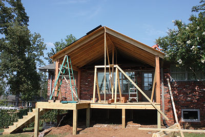 The roof is erected over a deck that will be screened as an outdoor living area.