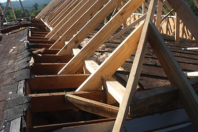 When necessary to tie the new rafters into the house framing, the workers cut into the old roof to make the secure connections.