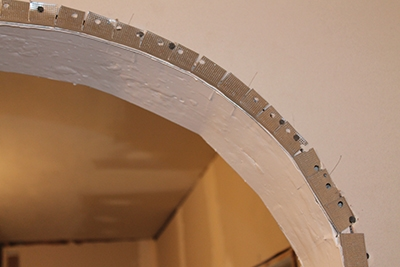 During the drywall phase, multiple sequential cuts were made in the corner bead so it would bend around the curve of the archway.