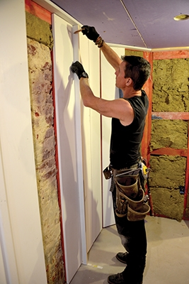 There's no need to measure or plumb the battens (1x2). Turn them on edge along a board edge, mark the wall and install on the marks.