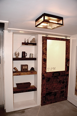 Frosted glass (Krylon frosted glass spray) and reclaimed lumber rock this cubby under the stairs.