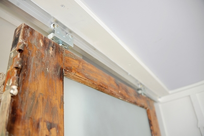 Hacking the wall-mount rolling door hardware to affix to the ceiling made hanging these doors possible.