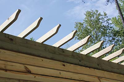 On top of the rafters, a layer of 2x4 purlins are installed at 90 degrees to the rafters and fastened in the same manner.