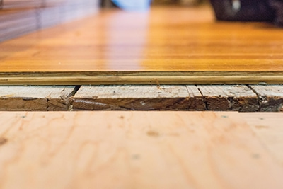 "After addressing moisture issues in the crawlspace beneath the floor, the next order of business was to prep the subfloor. To raise the height of the new finished floor to match an adjacent room, we installed a layer 1/2"" CDX plywood followed by 1/4"" sleepers."