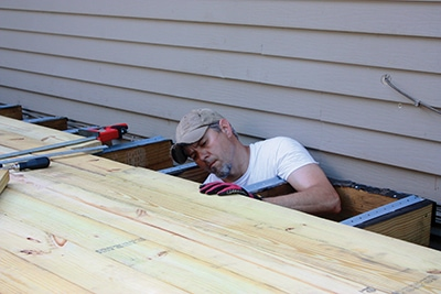 In tight spots, support your weight with an arm draped over a joist while you fasten the nearest board.