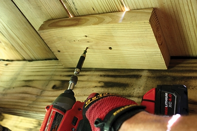 For boards ends that were spliced over the joists but not fastened to the tracks we installed under-deck blocking and cinched down the boards with screws from below.