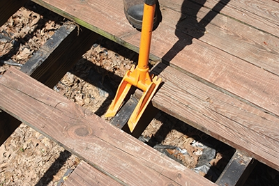 The Guster bridges over joists to pry up the decking with its forked demolition head.