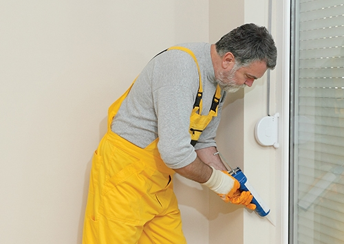 Construction worker caulking door or window with silicone glue using cartridge