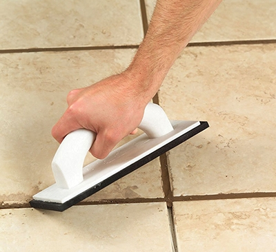 To use a rubber grout float, hold it at a 45-degree angle to the joint, spread the grout diagonally, and press firmly to ensure the joint is completely filled.