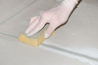 Use a damp sponge to clean excess grout as you apply it. Be prepared to repeat this procedure the day after installation. A sponge with an abrasive pad helps to scrub off dried grout sand and residue. Picture © thodonal/123RF