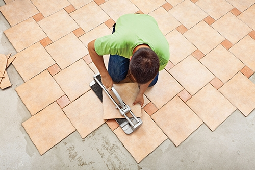 22247609 - man laying ceramic floor tiles working with a cutter device - top view