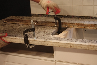 NOte the angle-iron bracing clamped across the length of the countertop to stabilize and reinforce its shape. This is kparticularly important for the section with the sink cut-out, which has a weakened center area since the granite is missing.