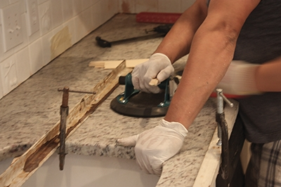The installers adjusted the counter-top's position with suction cups.