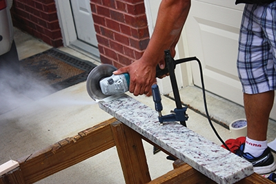 Small cuts can be made to granite backsplash material using a grinder with a diamond-grit blade.