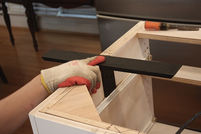 This support extends inside and outside the kitchen island's cabinet base.