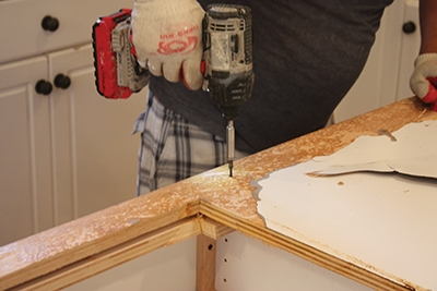 Pry up the old laminate and remove any screws hidden beneath it.
