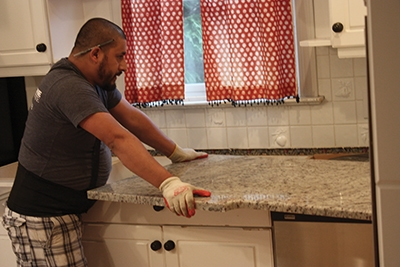 Carefully set the new granite countertop section in place on the cabinet base.