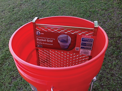 Using a paint grid inside a 5-gallon bucket proved to be the most efficient way to reload he roller when painting the roof.