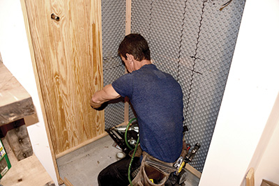 After coating their backs with Spar Urethane, the tongue-and-grove cladding is installed as the shower surround.
