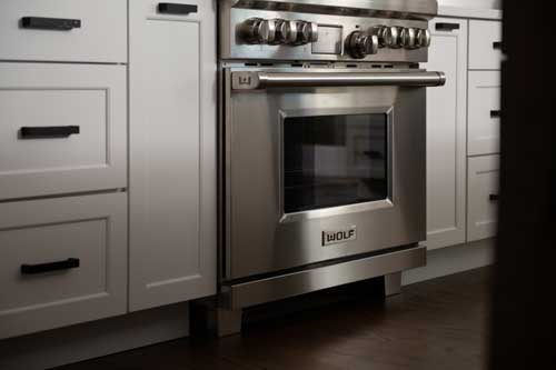wolf stove and white shaker stock cabinets