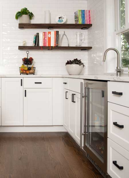 floating wooden shelves in white kitchen with stock cabinets and built in custom wine cooler